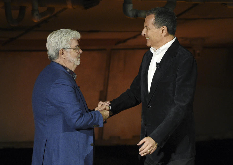 """""""Star Wars"""" film franchise creator George Lucas, left, shakes hands with Walt Disney Co. Chairman and CEO Bob Iger during a dedication ceremony for the new Star Wars: Galaxy's Edge attraction at Disneyland Park, Wednesday, May 29, 2019, in Anaheim, Calif. (Photo by Chris Pizzello/Invision/AP)"""