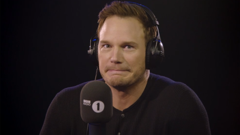 Actor Chris Pratt looks confused and shrugs at the camera in a radio stufio
