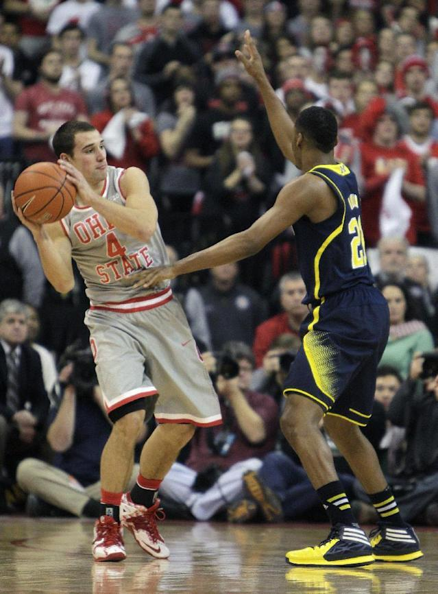 Ohio State's Aaron Craft, left, looks for an open pass as Michigan's Zak Irvin defends during the first half of an NCAA college basketball game Tuesday, Feb. 11, 2014, in Columbus, Ohio. (AP Photo/Jay LaPrete)