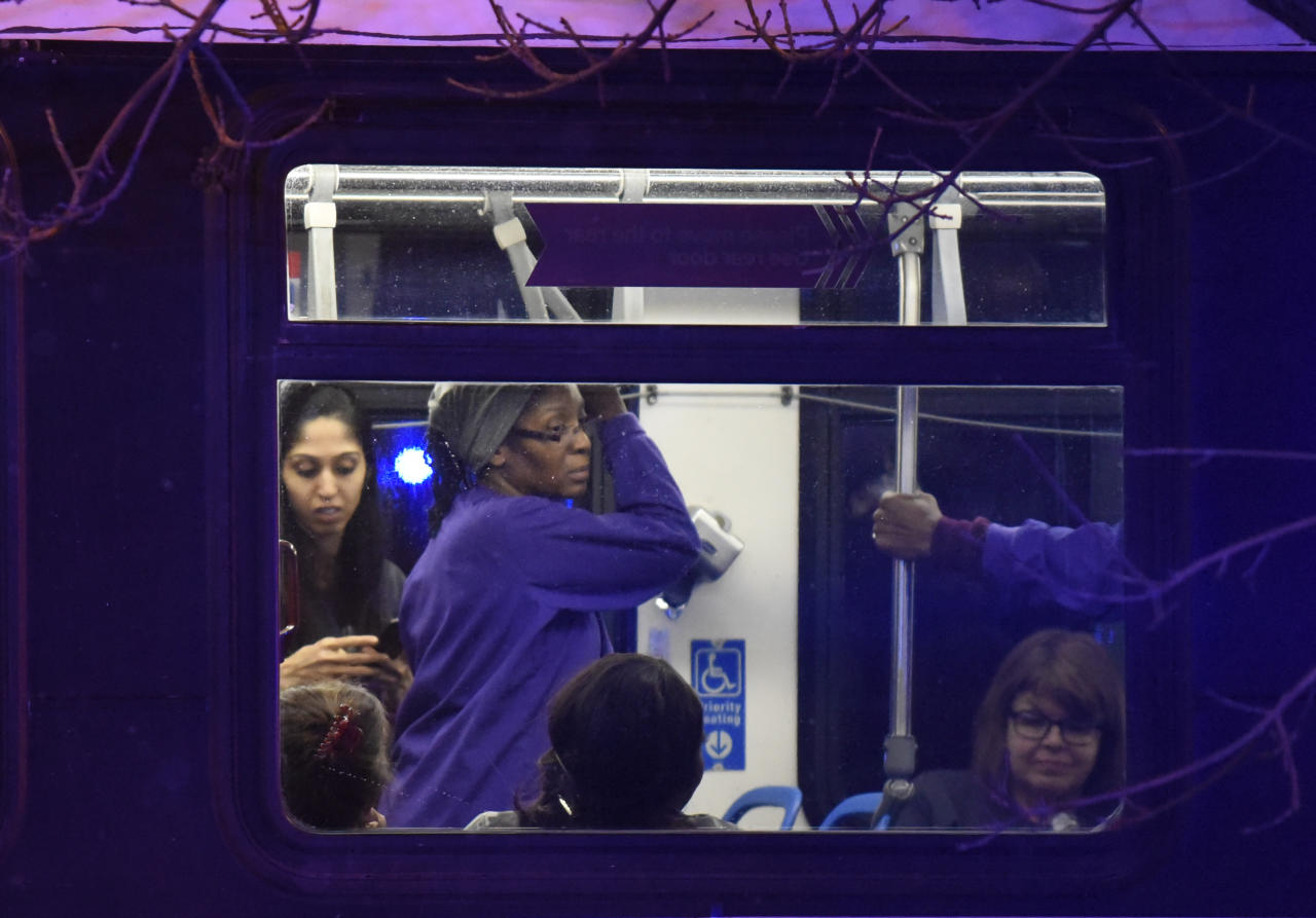 Employees from the hospital ride a Chicago Transit Authority bus after being evacuated from Mercy Hospital where shots were fired Monday, Nov. 19, 2018, in Chicago. A police spokesman said the gunman was dead, but it was not immediately clear if he took his own life or was killed by police at the hospital on the city's South Side. (AP Photo/David Banks)
