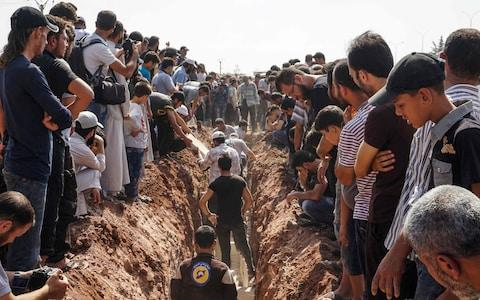 Members of the Syrian civil defence volunteers, also known as the White Helmets, bury their fellow comrades during a funeral in Sarmin, Idlib - Credit: AFP