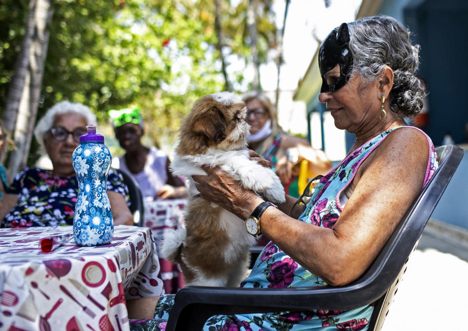 "An elderly woman holds a dog named Cristal at the ""Casa de Repouso Laços de Ouro"" nursing home in Sepetiba, Brazil, Thursday, Oct. 1, 2020. The Golias organization brought the animals, who they rescued from abandonment, to provide a little relief from the isolation many elderly people feel, cut off from friends and family due to fear of contagion from the new coronavirus. (AP Photo/Bruna Prado)"