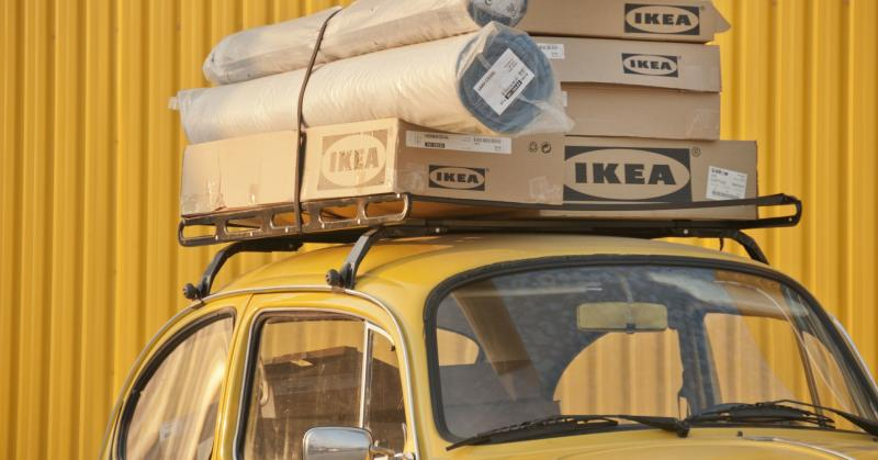 A group of Ikea boxes piled on top of an old fashioned VW car.