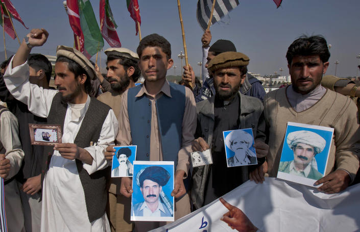 Pakistani tribal villagers hold pictures of their family members allegedly killed in U.S. drone attacks during a rally near parliament house in Islamabad, Pakistan on Saturday, Feb, 25, 2012. Dozens of tribal villagers form Waziristan region rallied in the capital Islamabad against drone attacks in Pakistani tribal areas. (AP Photo/Anjum Naveed)