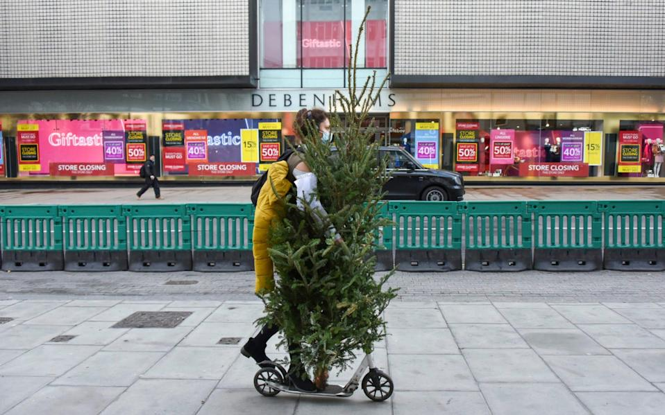 A woman wears a face mask as she carries a Christmas tree on a scooter, along the main shopping street of Oxford Street that remains nearly empty in central London -  Alberto Pezzali  / AP