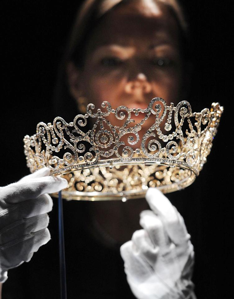 This Thursday June 28, 2012 photo shows curator Caroline de Guitaut, holding the Delhi Durbar Tiara, on show for the first time and made to mark the succession of King George V as King Emperor in 1911, at a new exhibition at Buckingham Palace, London. The new exhibition at Buckingham Palace shows jewels collected by six monarchs over three centuries to mark the Queen's Diamond jubilee this summer. (AP Photo/Stefan Rousseau/PA Wire) UNITED KINGDOM OUT
