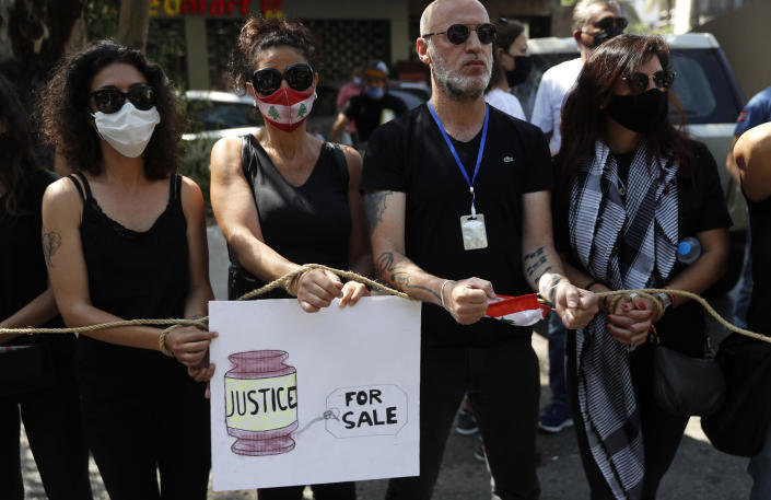Lebanese anti-government activists protest outside a Lebanese court, as they demanding the improving judicial independence, in Beirut, Lebanon, Wednesday, June 17, 2020. A year after anti-government protests roiled Lebanon, dozens of protesters are being tried before military courts that human rights lawyers say grossly violate due process and fail to investigate allegations of torture and abuse. (AP Photo/Hussein Malla)
