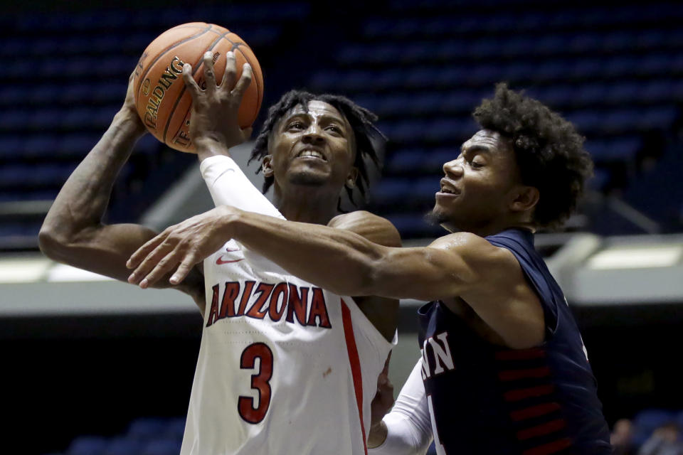 Arizona guard Dylan Smith, left, gets fouled by Penn guard Lucas Monroe going to the basket during the second half of an NCAA college basketball game at the Wooden Legacy tournament in Anaheim, Calif., Friday, Nov. 29, 2019. (AP Photo/Alex Gallardo)