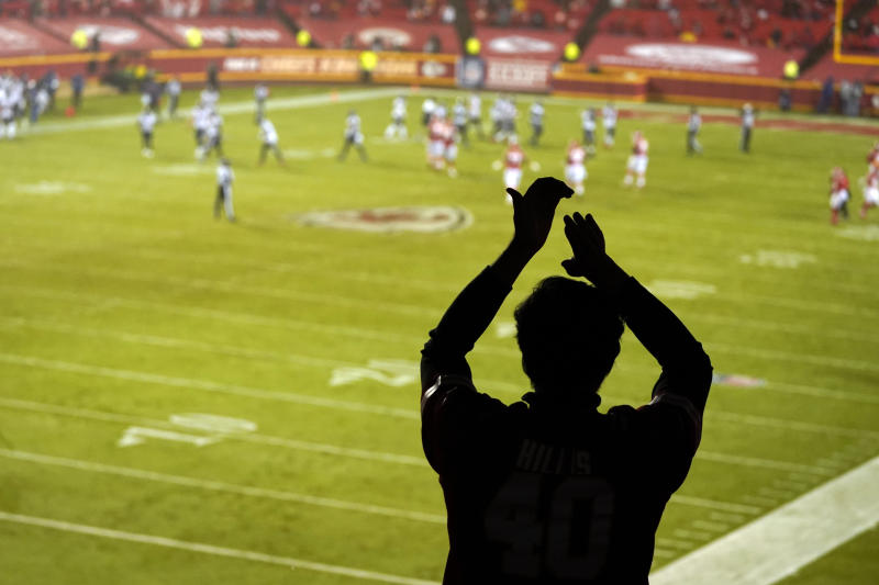 A silhouette of a fan clapping while football action takes place on the field.