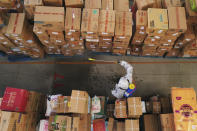 In this photo released by Xinhua News Agency, a worker wearing a protective suit sprays disinfectant the goods at a logistic distribution center in Shijiazhuang in north China's Hebei province on Saturday, Jan. 23, 2021. A Chinese city has brought 2,600 temporary treatment rooms online as the country's north battles new clusters of coronavirus. (Mu Yu/Xinhua via AP)