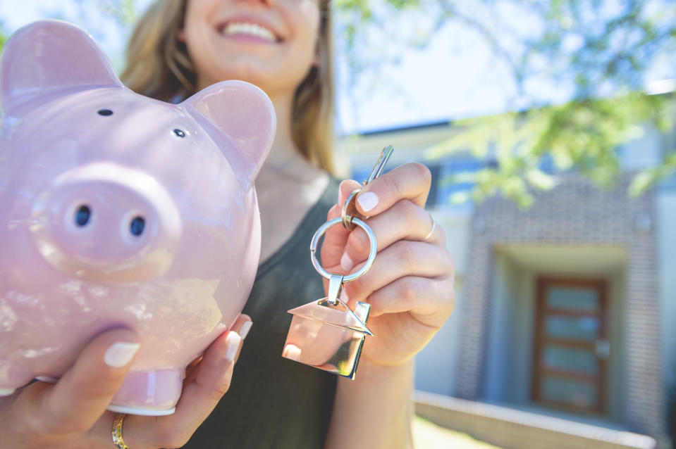 Hand holding a house key and piggy bank in front of a large house. The key ring has a house shaped icon on the end and is shiny silver colour. You can see the front door in the background. The key ring house icon is dangling down. Close up with shallow focus and copy space. Savings and New house concept.