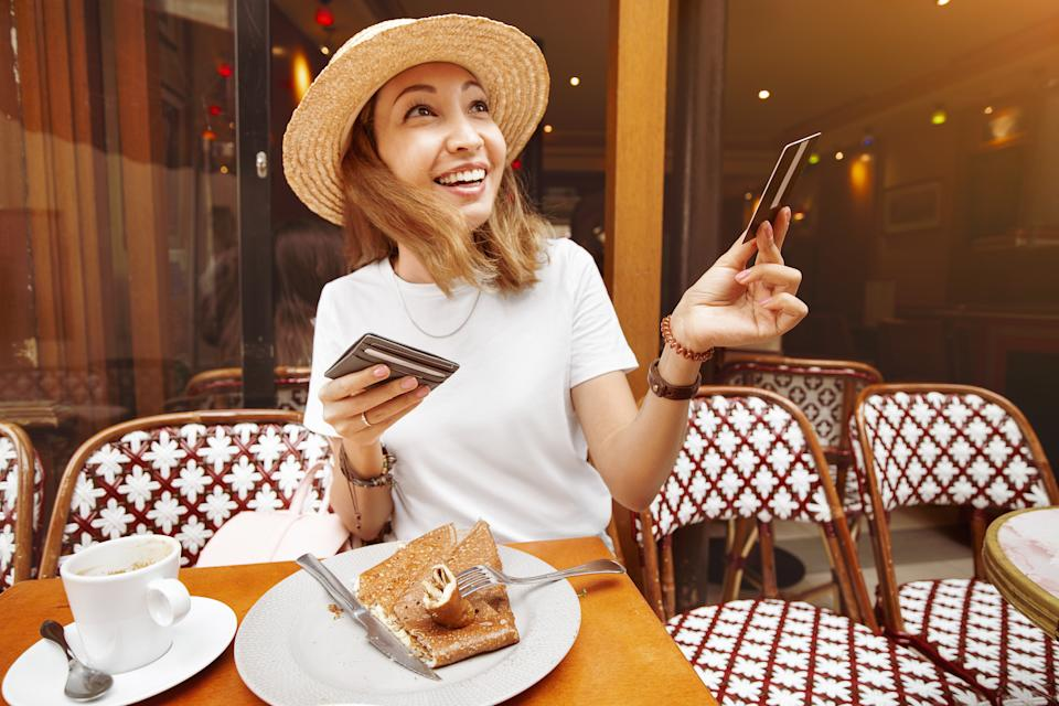 Girl finishes breakfast in a retro cafe in Paris and pays for lunch by credit card.