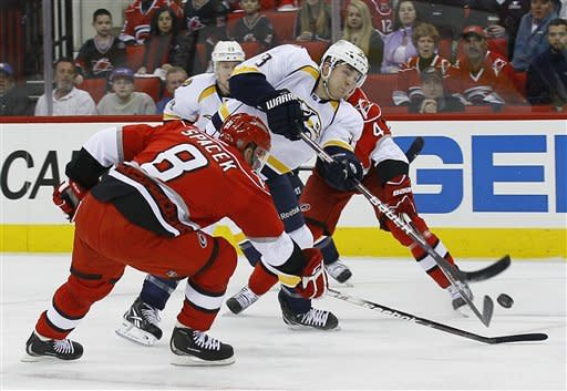 Carolina Hurricanes' Jaroslav Spacek (8), of the Czech Republic, and Jamie McBain (4) defend against Nashville Predators' Colin Wilson during the first period of an NHL hockey game in Raleigh, N.C., Tuesday, Feb. 28, 2012. (AP Photo/Gerry Broome)
