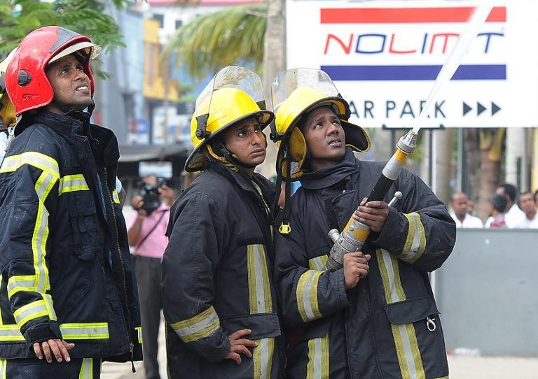 Sri Lankan firemen put out a fire at a Muslim-owned clothing store in Panadura on June 21, 2014
