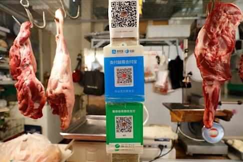QR codes of the digital payment services WeChat Pay and Alipay seen at a meat stall at a fresh market in Beijing on August 8. Photo: Reuters