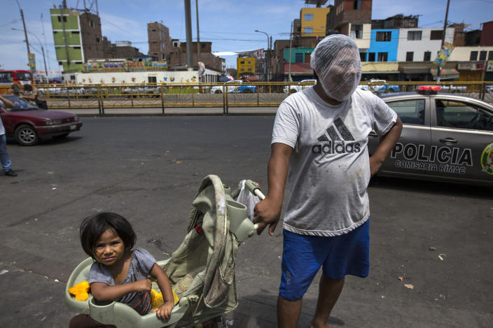 In this March 19, 2020 photo, Luis Mendoza jokingly dons a hair net over his face given to him by a group handing out protective gear outside a popular market where he has come to beg for food with his 2-year-old daughter Alejandra, in Lima, Peru. The global COVID-19 pandemic has spotlighted the wide gap between the rich and poor in Latin America and economists say a looming economic recession worse than any since World War II could push the continent's long-suffering poor into even more dire circumstances. (AP Photo/Rodrigo Abd)