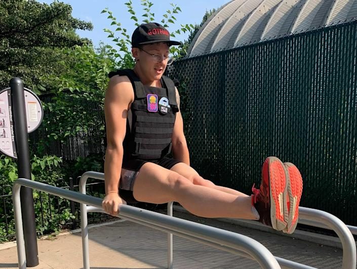 an athlete in a weighted vest holding an L-sit position on a set of parallel bars in a sunny park