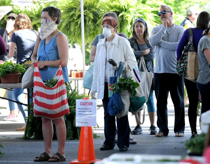 Some shoppers wear face masks while browsing at the Franklin Farmers Market in Franklin, Tenn.