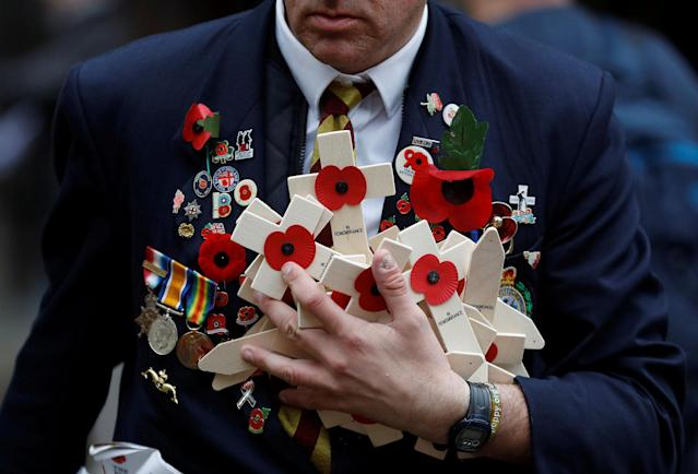 <p>Member of the Royal British Legion carries wooden crosses adorned with poppies at the Field of Remembrance in London, Britain, Nov. 11, 2017. (Photo: Peter Nicholls/Reuters) </p>