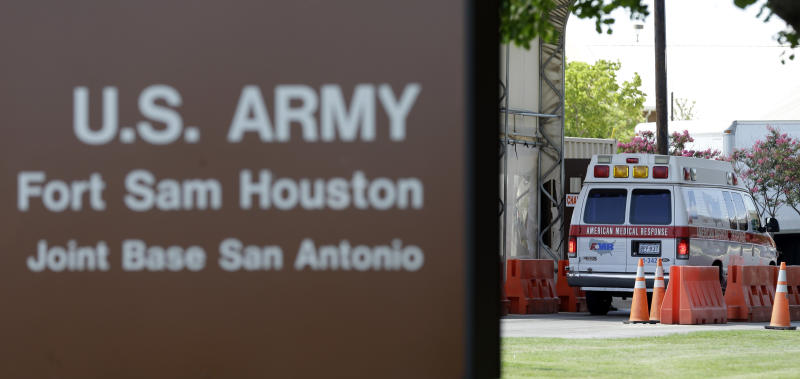 An ambulance enter at a gate to Fort Sam Houston, Monday, June 10, 2013, in San Antonio. San Antonio police have arrested a gunman for shooting at the main gate of the U.S. Army post. (AP Photo/Eric Gay)