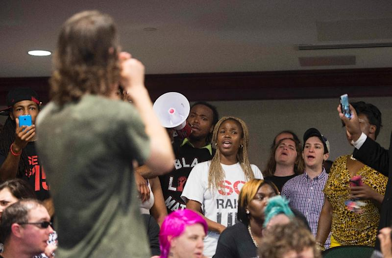 Protesters stand up and chant in the hearing room of City Hall in Charleston, South Carolina on April 8, 2015, after the white police officer who fatally shot a fleeing black man in North Charleston has been fired and charged with murder (AFP Photo/Jim Watson)