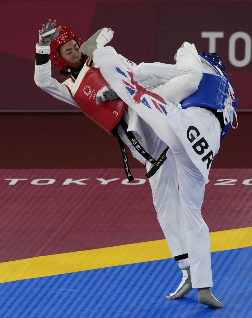 Kimia Alizadeh Zonoozi, Refugee Olympic Team, is attacked by Britain's Jade Jones during the taekwondo women's 57kg match at the 2020 Summer Olympics, Sunday, July 25, 2021, in Tokyo, Japan. (AP Photo/Themba Hadebe)