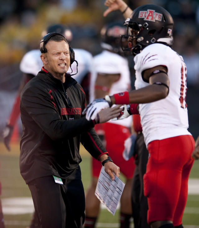 FILE - In this Sept. 28, 2013 file photo, Arkansas State head coach Bryan Harsin, left, encourages his player Phillip Butterfield, right, during the second quarter of an NCAA college football game against Missouri in Columbia, Mo. A person familiar with the decision tells The Associated Press that Boise State has hired Harsin as its next coach. The person spoke on condition of anonymity because the move had not become official. (AP Photo/L.G. Patterson, File)