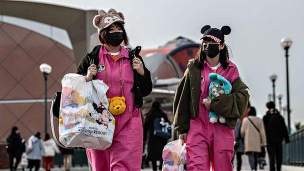 PHOTO: Two women leave Tokyo Disneyland on the day it announced it will close until March 15th because of concerns over the COVID-19 virus, on Feb. 28, 2020 in Japan. (Carl Court/Getty Images)