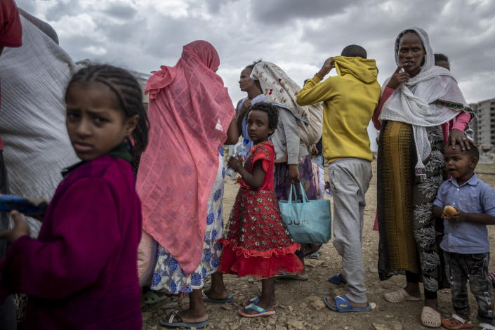 Elena, 7, center, stands in line with other displaced Tigrayans to receive food donated by local residents at a reception center for the internally displaced in Mekele, in the Tigray region of northern Ethiopia, on Sunday, May 9, 2021. In farming areas in Tigray to which The Associated Press got rare access, farmers, aid workers and local officials confirmed that food had been turned into a weapon of war. (AP Photo/Ben Curtis)