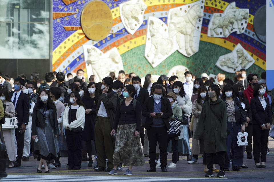 People wearing protective masks to help curb the spread of the coronavirus walk along a pedestrian crossing in Shibuya district in Tokyo on April 7, 2021. Japan is set to strengthen anti-virus measures in Tokyo on Friday, April 9, 2021 to curb the rapid spread of a more contagious coronavirus variant just three months before the Olympics begin in the capital where most people are not yet vaccinated. (AP Photo/Eugene Hoshiko)