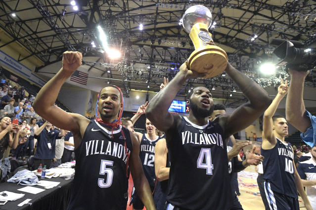 Villanova guard Phil Booth (5) and forward Eric Paschall (4) celebrate with the championship trophy after getting a 66-60 win over Florida State in the championship game of an NCAA college basketball tournament Sunday, Nov. 25, 2018, in Lake Buena Vista, Fla. (AP Photo/Phelan M. Ebenhack)