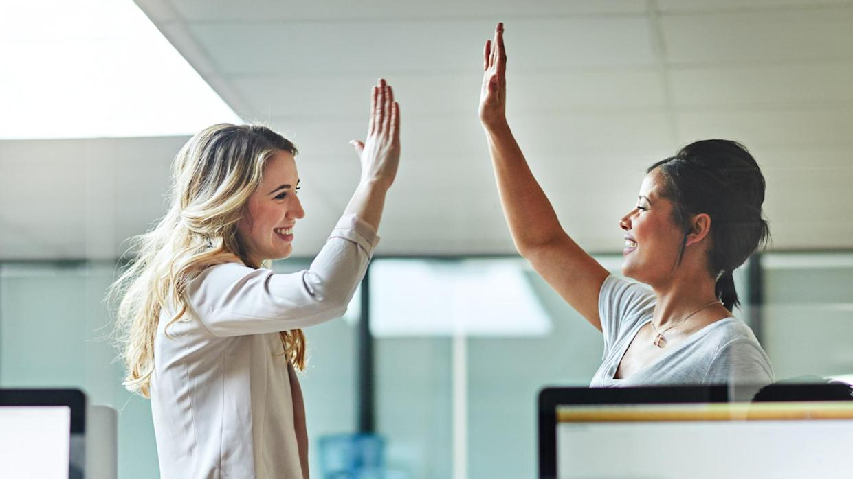 Shot of two colleagues giving each other a high five at work.