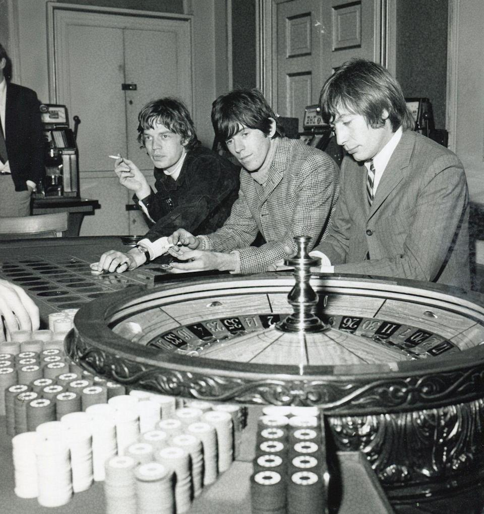 <p>From left, British musicians Mick Jagger, Keith Richards, and Charlie Watts, all of the group the Rolling Stones, sit together at a roulette table, Isle of Man, September 13, 1965.</p>
