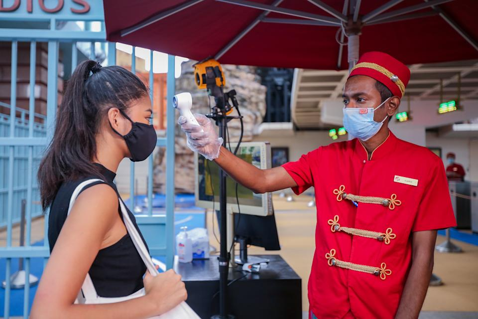 A posed photo of a Universal Studios Singapore employee checking the temperature of a guest with a thermometer. Resorts World Singapore attractions on Sentosa, including Universal Studios Singapore and the S.E.A. Aquarium, will reopen in Phase 2 of Singapore's reopening during the COVID-19 pandemic. (Photo: RWS)