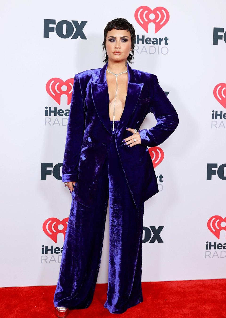 We can't get over how good Demi Lovato looks with their new mullet! Styled by Siena Montesano, they looked powerful in a crushed velvet pantsuit by Dundas. Demi kept the violet theme consistent with their intense smokey eye and metallic purple nails. The star ditched wearing a shirt and instead opted for a bare chest adorned with a string of bling.