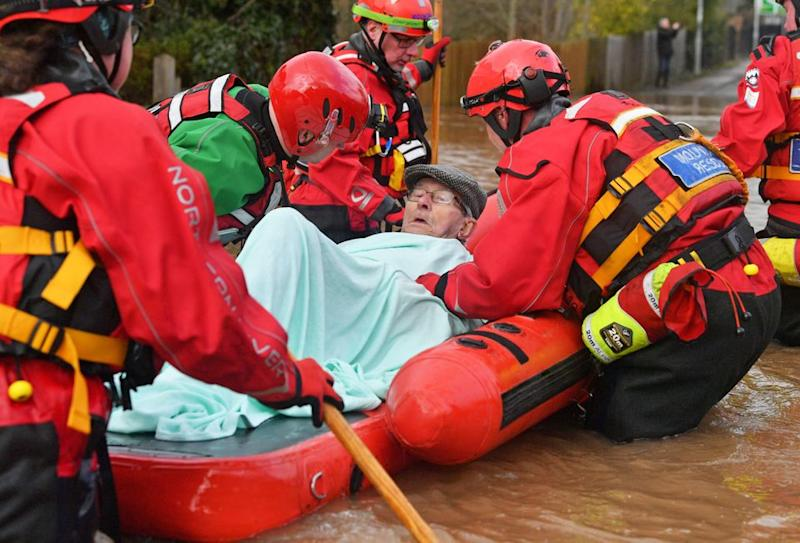 Mountain Rescue team members rescue Peter Morgan from his house where he has lived his whole life, which has been flooded in Monmouth