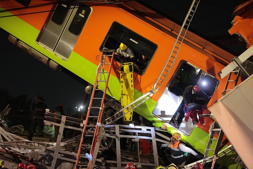 Emergency personnel search for accident survivors in a tilted subway car at night.
