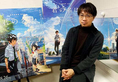 FILE PHOTO - Japanese anime director Makoto Shinkai poses for a photo in front of posters of his animated film 'Your Name' after an interview with Reuters in Tokyo
