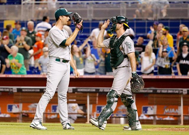 Jeff Francis of the Oakland Athletics high-fives John Jaso after defeating the Miami Marlins on June 28, 2014 in Miami, Florida (AFP Photo/Rob Foldy)