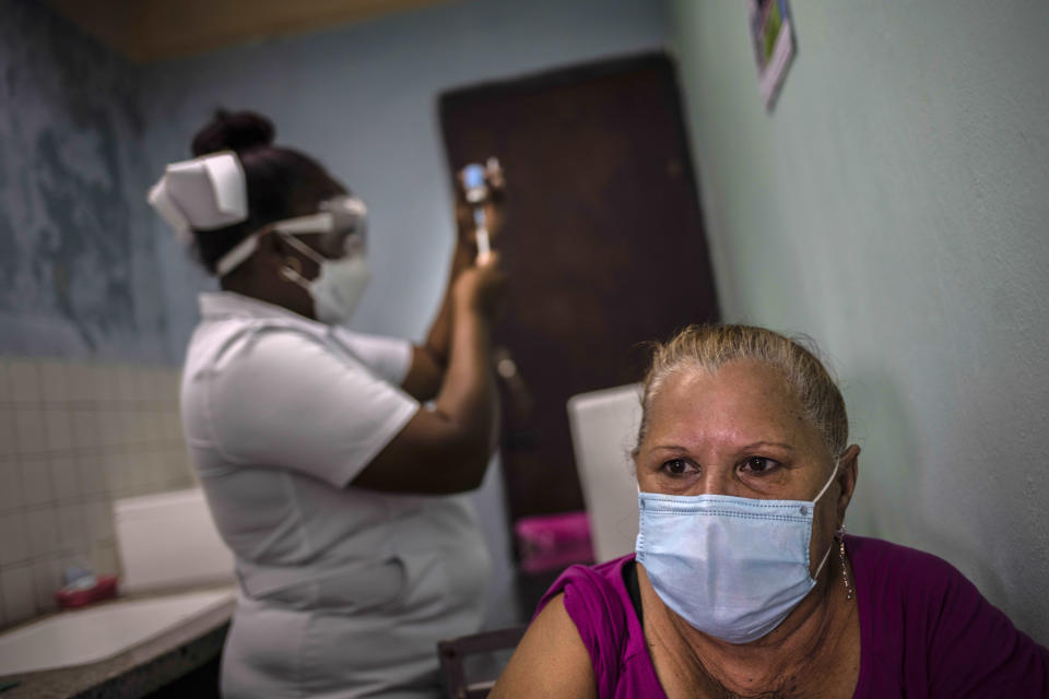 A woman waits to be vaccinated as a nurse prepares the dose of the Cuban Abdala vaccine for COVID-19 at a doctors' office in Alamar on the outskirts of Havana, Cuba, Friday, May 14, 2021. Cuba has begun to immunize people this week with its own vaccines, Abdala and Soberana 02, the only ones developed by a Latin American country. (AP Photo/Ramon Espinosa)