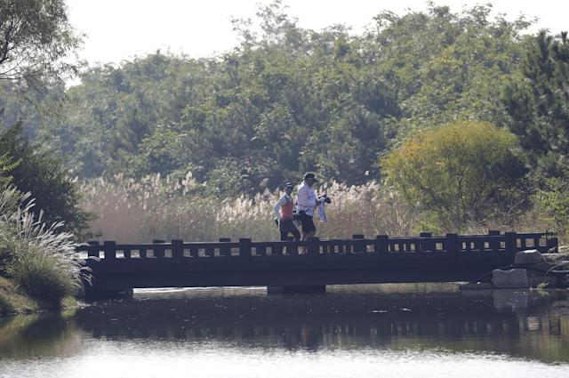 Ayako Uehara of Japan crosses a bridge with her caddie during the first round of the KEB HanaBank Championship golf tournament at Sky72 Golf Club in Incheon, west of Seoul, South Korea, Friday, Oct. 18, 2013. (AP Photo/Lee Jin-man)