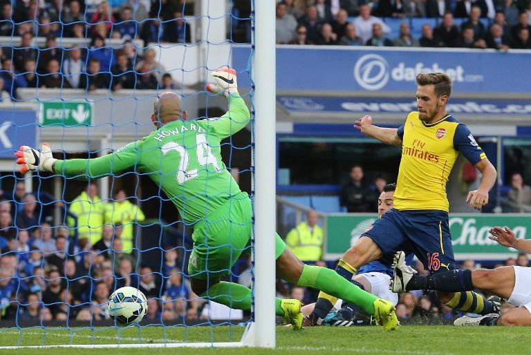 Aaron Ramsey (R) scores Arsenal's first goal past Everton goalkeeper Tim Howard during their Premier League match at Goodison Park on August 23, 2014