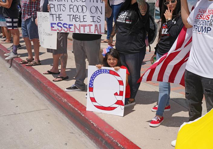"""A child with a QAnon sign at an anti-lockdown rally in Huntington Beach, Calif., May 1, 2020. <span class=""""copyright"""">Jamie Lee Curtis Taete</span>"""