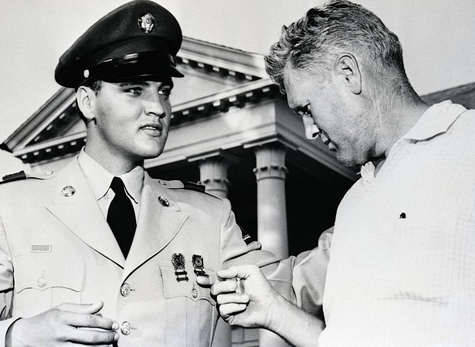 <p>In 1960, Presley was honorably discharged from the United States Army and returned home. After two years in service, the singer rose to the rank of Sargent and earned numerous medals. Here, his father Vernon admires his honors, while posing for a photo outside of Graceland. </p>