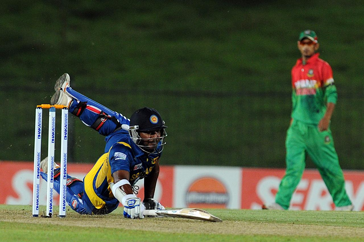 Sri Lanka cricketer Kumar Sangakkara dives to avoid being run out during the opening one-day international (ODI) match between Sri Lanka and Bangladesh at The Suriyawewa Mahinda Rajapakse International Cricket Stadium in the southern district of Hambantota on March 23, 2013.  Sri Lankan cricket captain Angelo Mathews  won the toss and elected to field. AFP PHOTO/ Ishara S. KODIKARA        (Photo credit should read Ishara S.KODIKARA/AFP/Getty Images)