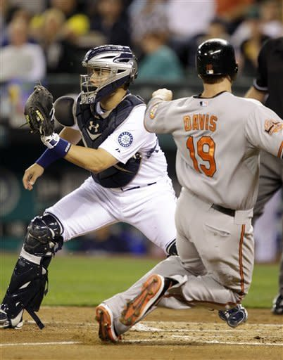 Baltimore Orioles' Chris Davis (19) scores in the fourth inning as Seattle Mariners catcher Jesus Montero waits for the throw during a baseball game, Wednesday, Sept. 19, 2012, in Seattle. (AP Photo/Ted S. Warren)