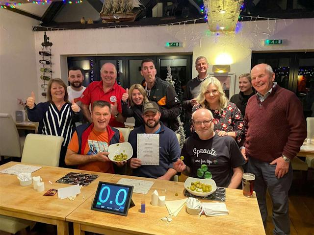 Wayne Sherlock (centre) with his fellow competitiors after breaking the world record for eating sprouts. [Photo: SWNS]