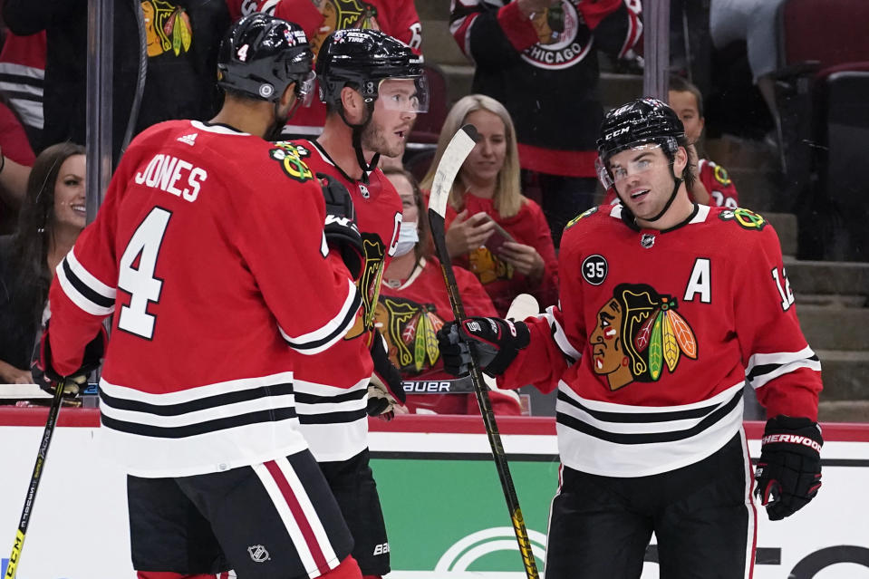 Chicago Blackhawks left wing Alex DeBrincat, right, celebrates with defenseman Seth Jones, left, and center Jonathan Toews after scoring a goal during the second period of an NHL preseason hockey game against the St. Louis Blues in Chicago, Friday, Oct. 1, 2021. (AP Photo/Nam Y. Huh)