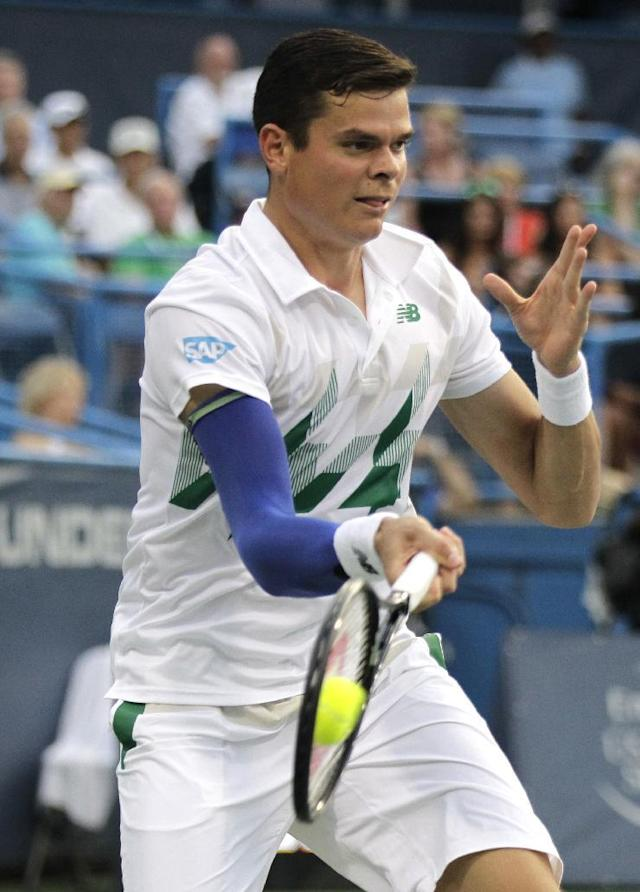 Milos Raonic, of Canada, returns the ball to Lleyton Hewitt, of Australia, at the Citi Open tennis tournament, Thursday, July 31, 2014, in Washington. (AP Photo/Luis M. Alvarez)