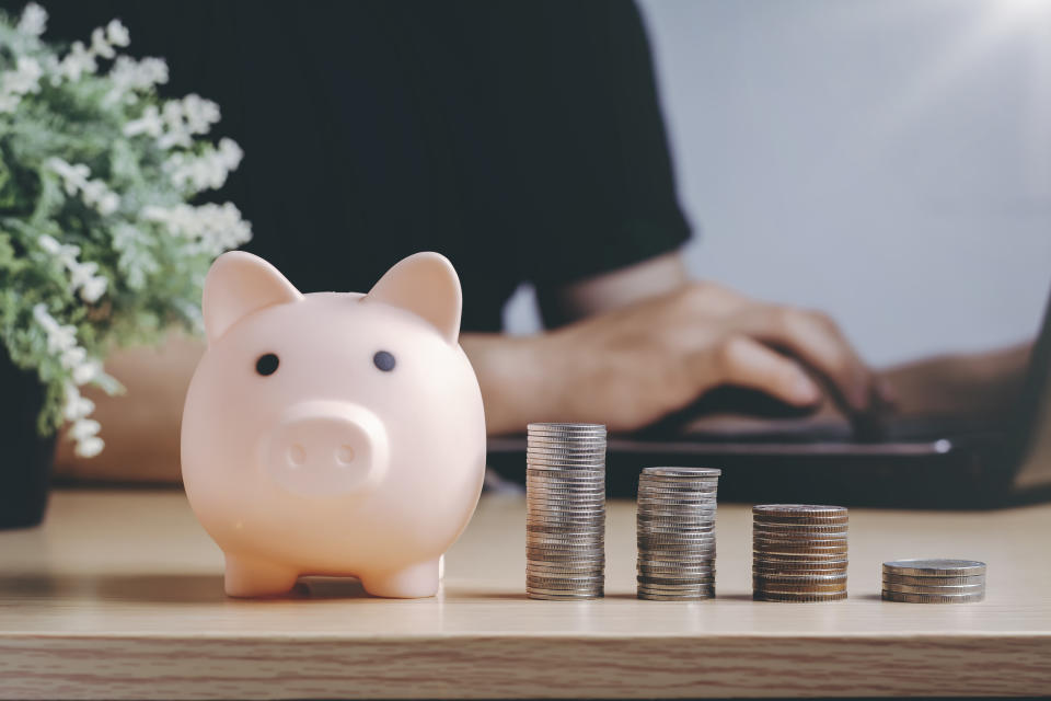 Saving money wealth and financial concept. Asian men working at home during the crisis are calculate family income and expenses, along with pension coins and piggy banks on wooden floors.